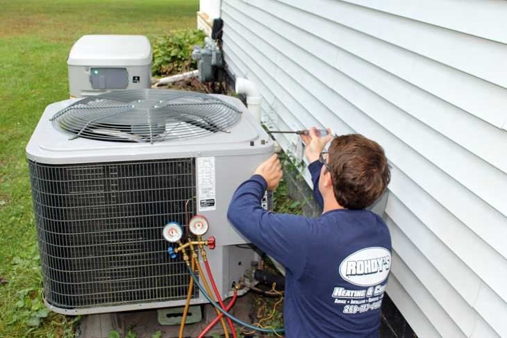 Image of service tech working on air conditioning unit